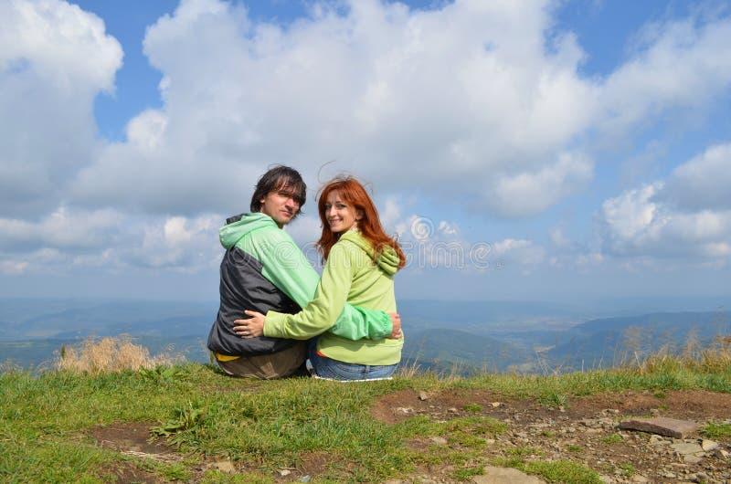 Touristes heureux d'homme blanc et de femme dans des vêtements verts se reposant au bord du dessus de la montagne et du regard à  photographie stock libre de droits