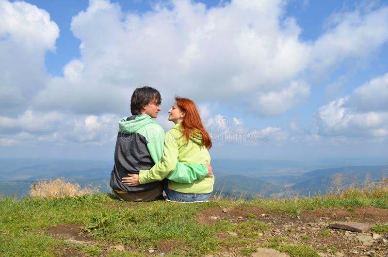 Touristes heureux d'homme et de femme dans des vêtements verts reposant étreindre au bord du dessus de la montagne et regarder l' image stock