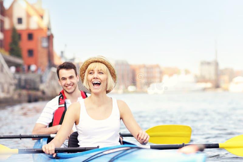 Touristes heureux dans un canoë photo stock
