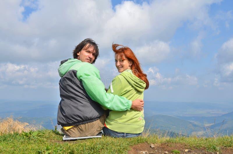 Touristes heureux de type et de fille dans des vêtements verts se reposant au bord du dessus de la montagne et du regard à la cam image stock