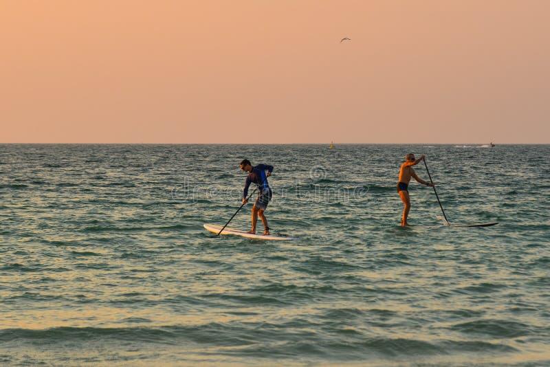 Touristes kayaking sur la mer au coucher du soleil images stock