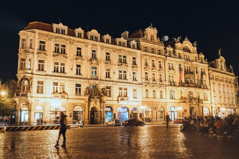Touristes méconnaissables marchant sur vieux hôtel de ville la nuit à Prague photo libre de droits