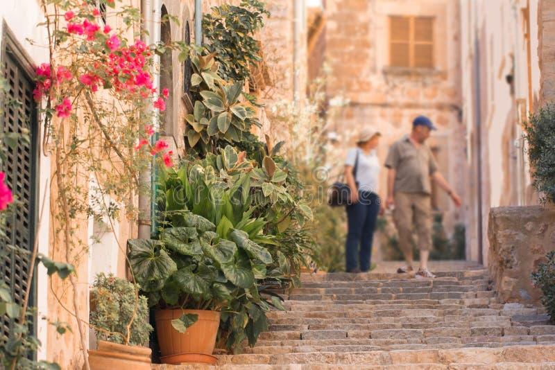 Touristes marchant sur la rue méditerranéenne typique en petite ville photographie stock