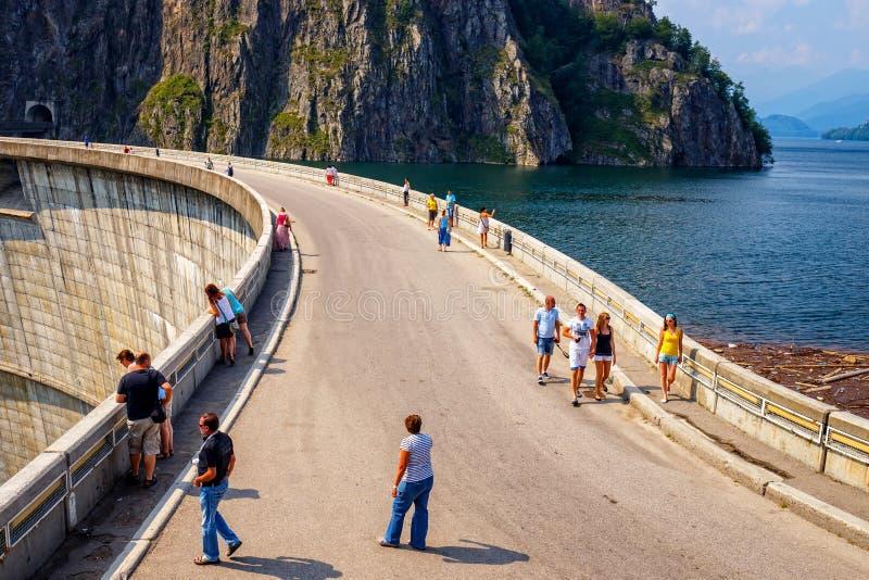 Touristes marchant sur le barrage de Vidraru sur le lac Vidraru dans le comté d'Arges photographie stock