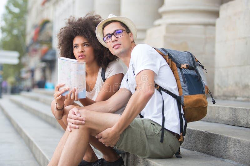 Touristes multi-ethniques de couples avec la carte dans la ville images stock