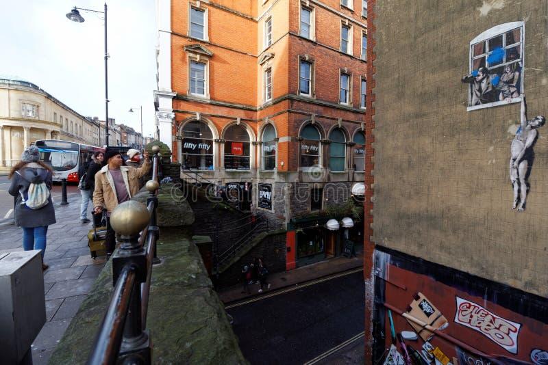 Touristes photographiant l'illustration de Banksy photos stock