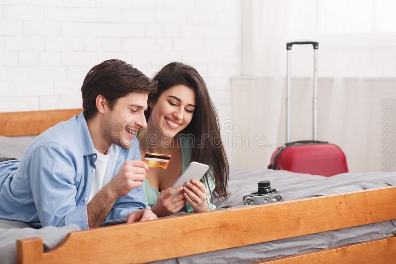 Touristes réservant des billets, utilisant le téléphone et la carte de crédit image stock