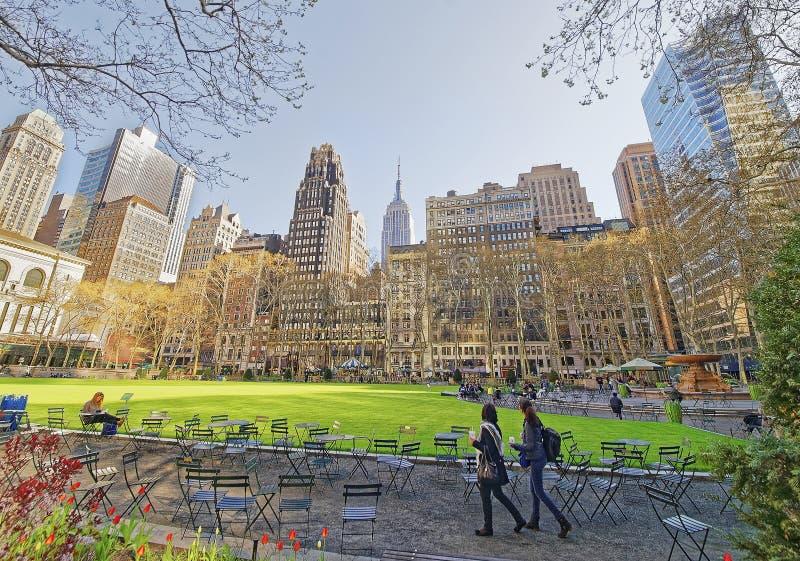 Touristes regardant la pelouse et les gratte-ciel verts en Bryant Park photo libre de droits