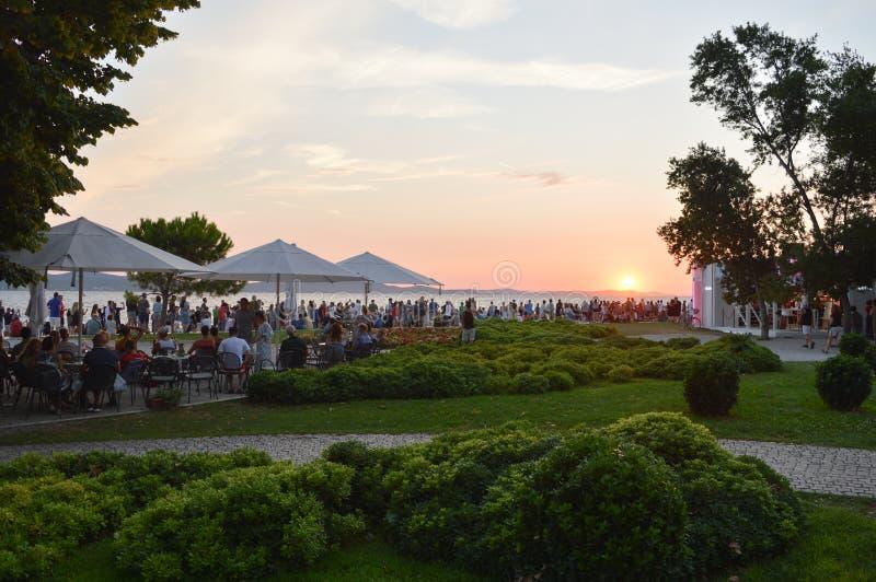 Touristes regardant le coucher du soleil dans Zadar image stock