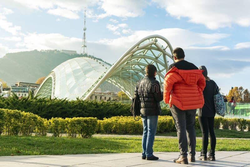 Touristes regardant le pont célèbre de Tbilisi de la paix et de la haute tour de TV à l'arrière-plan sur la colline photos stock