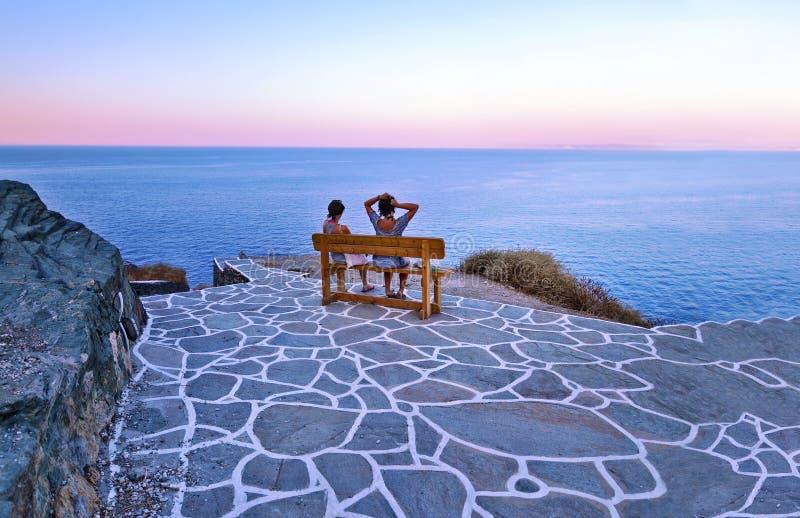 Touristes s'asseyant sur le banc au château Cyclades Grèce de Sifnos image stock
