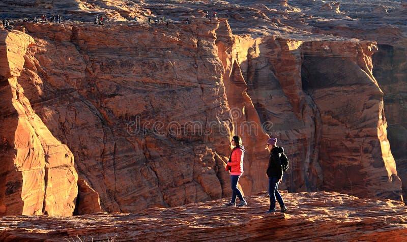 Touristes se tenant au bord des falaises à la courbure en fer à cheval photos libres de droits