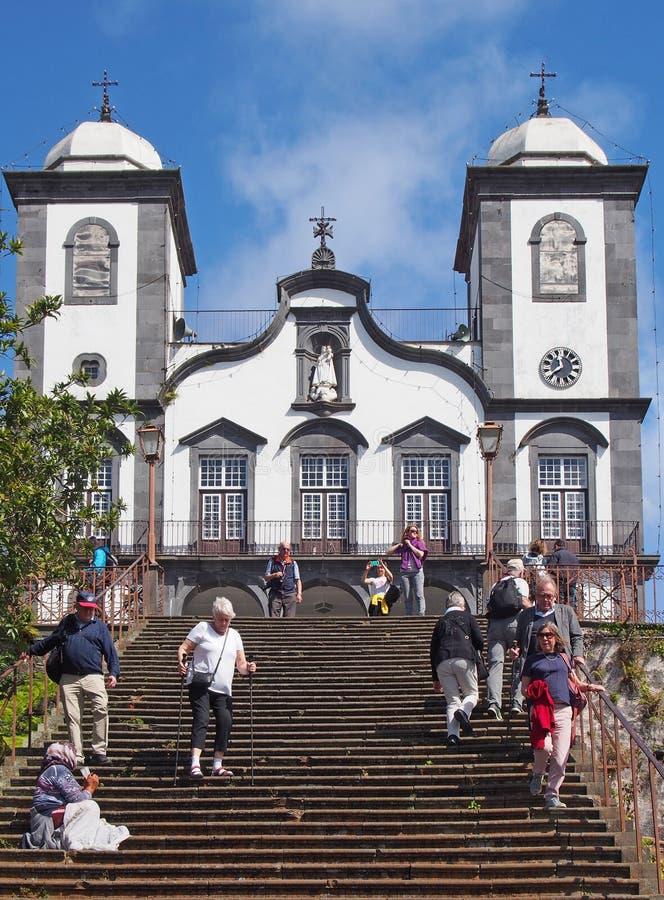 touristes sur les étapes de l'église historique de notre Madame de Monte à Funchal avec prier de dame âgée photographie stock
