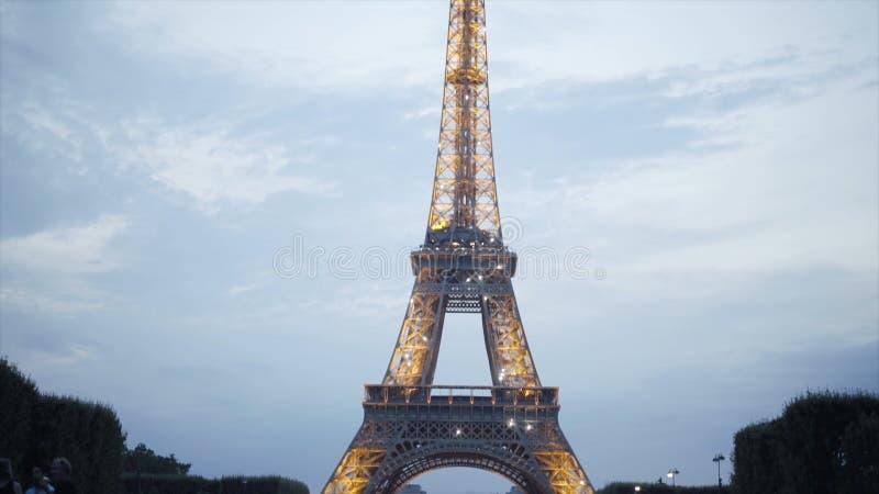 Touristes ? Tour Eiffel brillant dans la soir?e action Beaucoup de touristes s'asseyent sur la pelouse et appr?cient la belle vue photo libre de droits