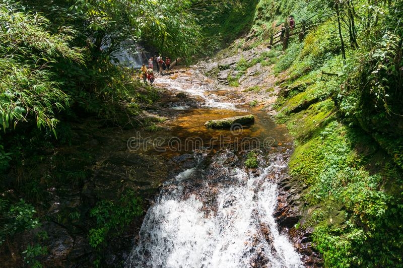 Touristes traversant la rivière rapide de montagne dans l'ecotouri d'or de courant image stock