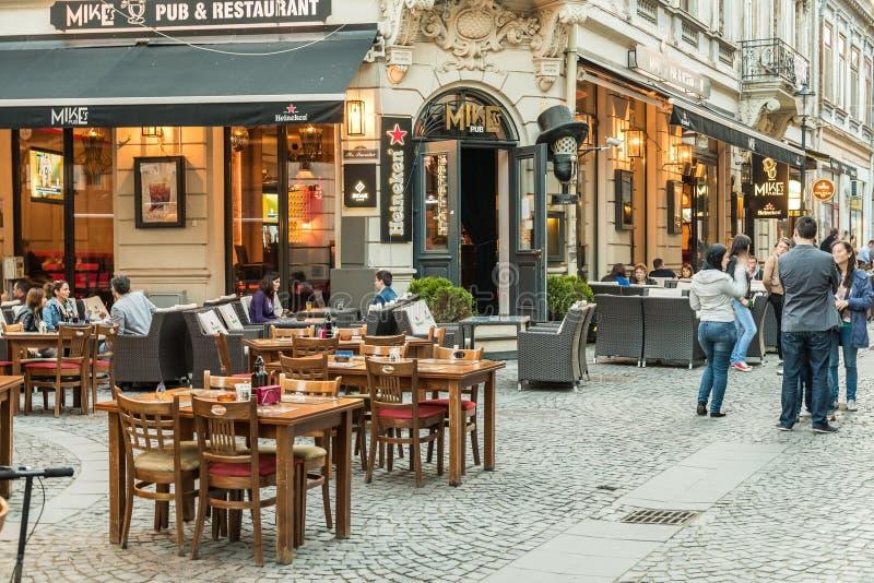Touristes visitant et prenant le déjeuner au centre ville extérieur de café de restaurant à Bucarest photo stock