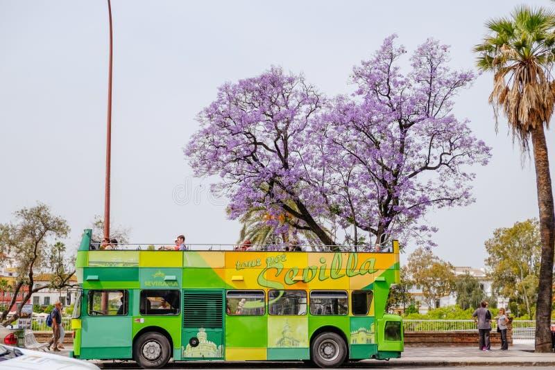 Touristes voyageant sur l'ouvert couvert houblon-sur le bus touristique d'houblon- Séville, Espagne photographie stock