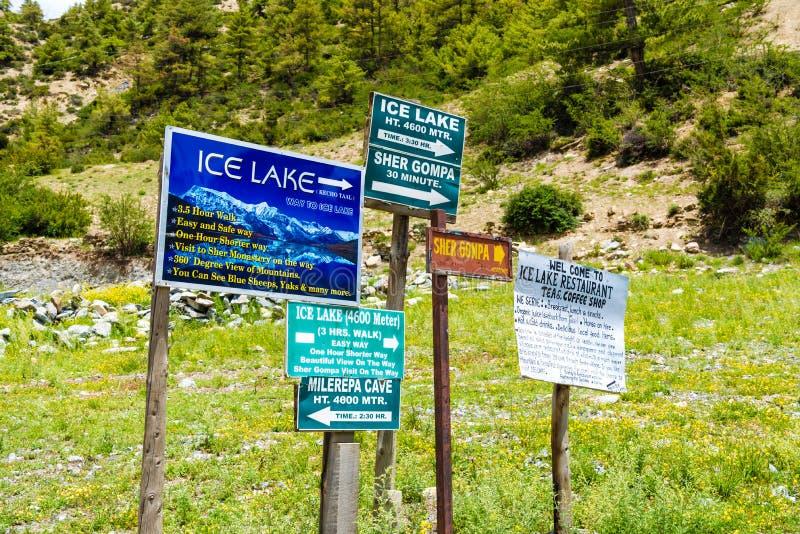 Touristic знаки информации на дороге к деревне на зоне консервации Annapurna, Непалу Manang стоковая фотография rf