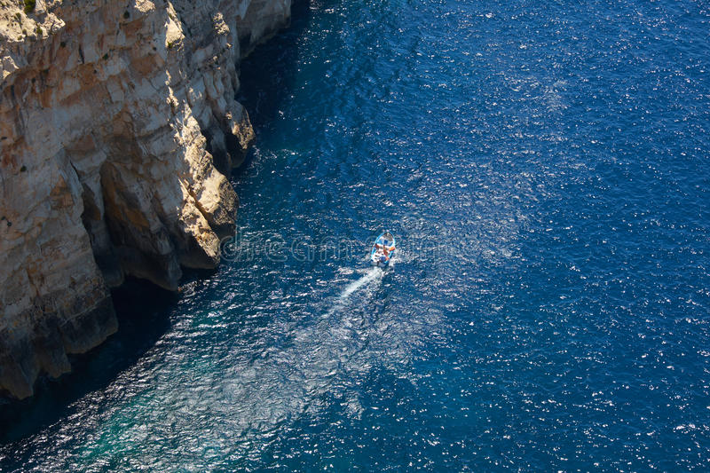 Touristic boat under steep cliff over Mediterranean sea on south royalty free stock photo