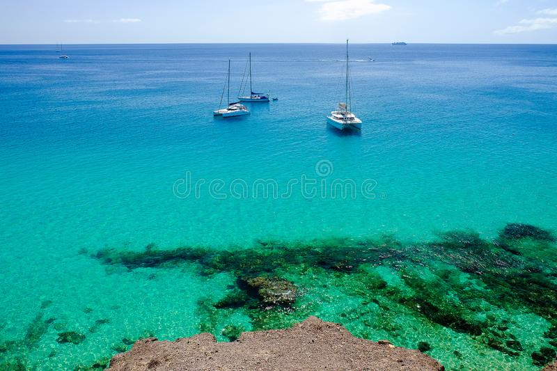 Touristic boats in Morro Jable Fuerteventura, Spain. View on the ocean with crystal water and three woutistic boats in Morro Jable on the Canary island stock image