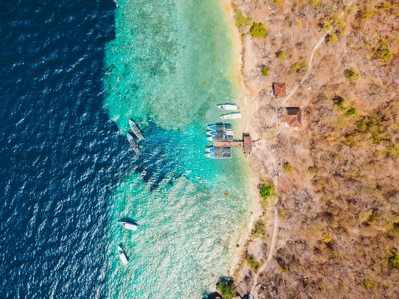 Touristic boats at the pier in blue ocean on Menjangan island. Aerial view. Touristic boats at the pier in blue ocean on Menjangan island royalty free stock photography
