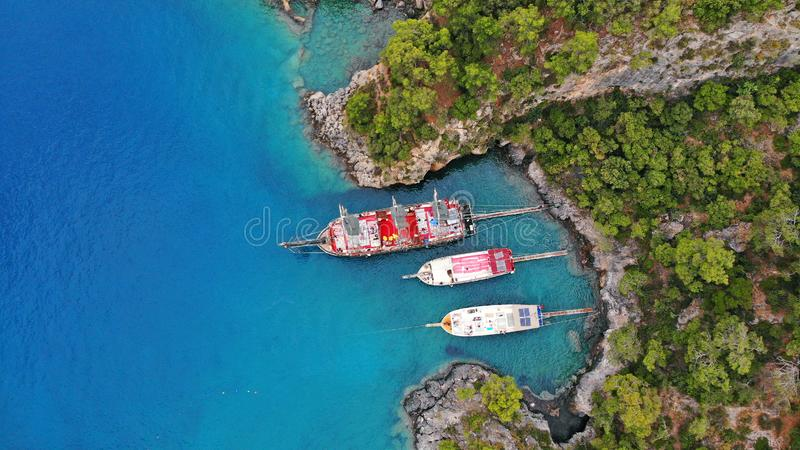 Touristic boats in the sea, top view. Aerial view of colorful boats standing abreast on the shore of the turquoise sea in azure water royalty free stock photography