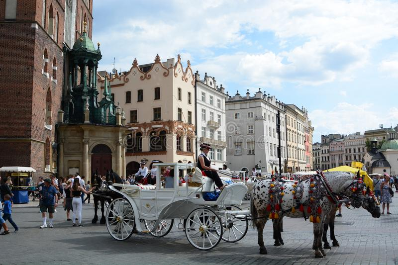 Touristic horse-drawn carriage in the main market square. Krakow. Poland. Kraków is the second largest and one of the oldest cities in Poland, situated on the royalty free stock photo