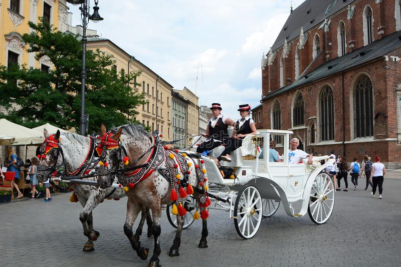 Touristic horse-drawn carriage at summer. Main market square. Krakow. Poland. Kraków is the second largest and one of the oldest cities in Poland, situated on stock photography