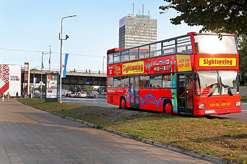 Touristic red double-decker hop-on hop-off City Sightseeing tour bus on the street of Riga city near embankment, Latvia. Europe stock photos