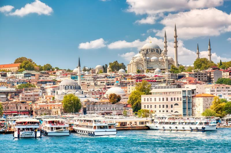 Touristic sightseeing ships in Golden Horn bay of Istanbul and view on Suleymaniye mosque with Sultanahmet district against blue. Sky and clouds. Istanbul royalty free stock photography