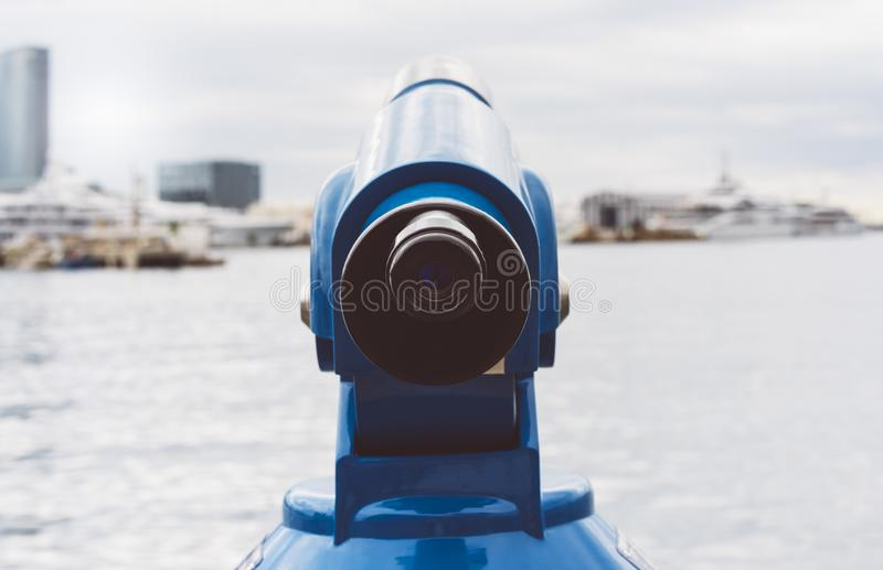 Touristic telescope look at the city and sea with sunset view of Barcelona Spain, close up old blue binoculars on background view. Point the pier port yacht stock photos