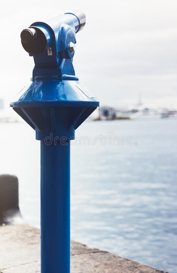 Touristic telescope look at the city and sea with sunset view of Barcelona Spain, close up old blue binoculars on background view. Point the pier port yacht royalty free stock photo