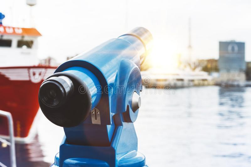 Touristic telescope look at city and sea with sunset view of Barcelona Spain, close up old blue binoculars on background viewpoint. The pier port red ship yacht royalty free stock photo