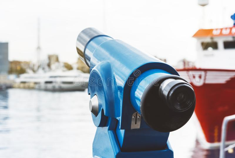 Touristic telescope look at city and sea with sunset view of Barcelona Spain, close up old blue binoculars on background viewpoint. The pier port red ship yacht royalty free stock images