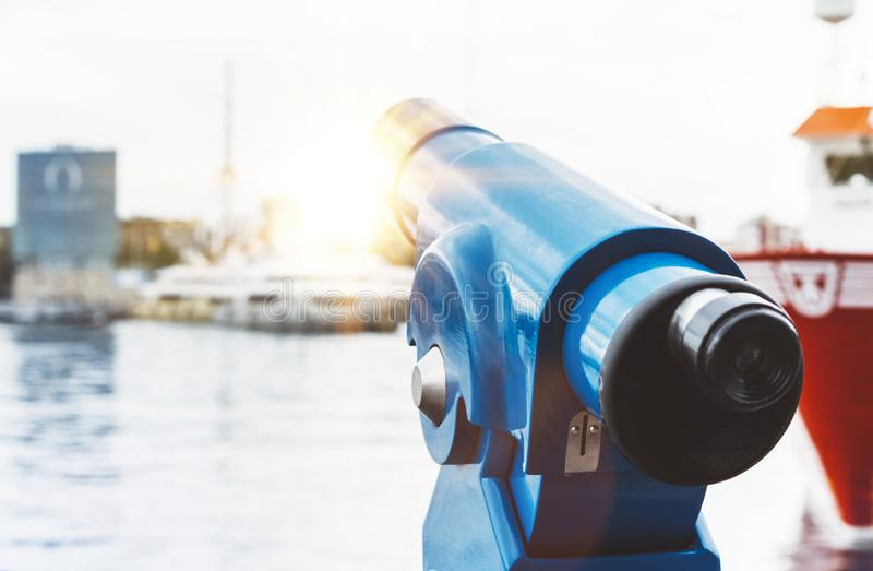 Touristic telescope look at city and sea with sunset view of Barcelona Spain, close up old blue binoculars on background viewpoint. The pier port red ship yacht royalty free stock photos