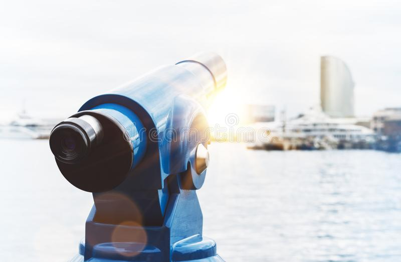 Touristic telescope look at city and sea with sunset view of Barcelona Spain, close up old blue binoculars on background viewpoint. The pier port yacht, coin stock photography