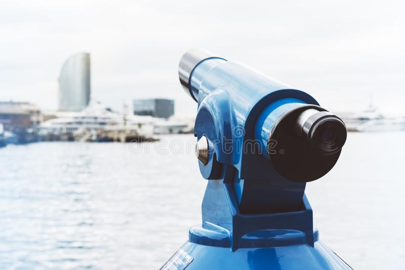 Touristic telescope look at city and sea with sunset view of Barcelona Spain, close up old blue binoculars on background viewpoint. The pier port yacht, coin stock photo