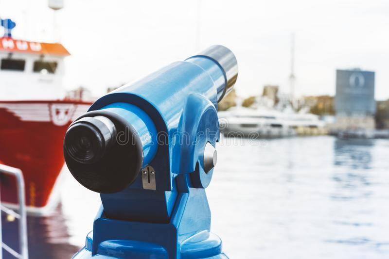 Touristic telescope look at city and sea with sunset view of Barcelona Spain, close up old blue binoculars on background viewpoint. The pier port red ship yacht stock photos