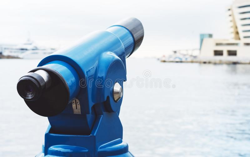 Touristic telescope look at city and sea with sunset view of Barcelona Spain, close up old blue binoculars on background viewpoint. The pier port yacht, coin royalty free stock photos