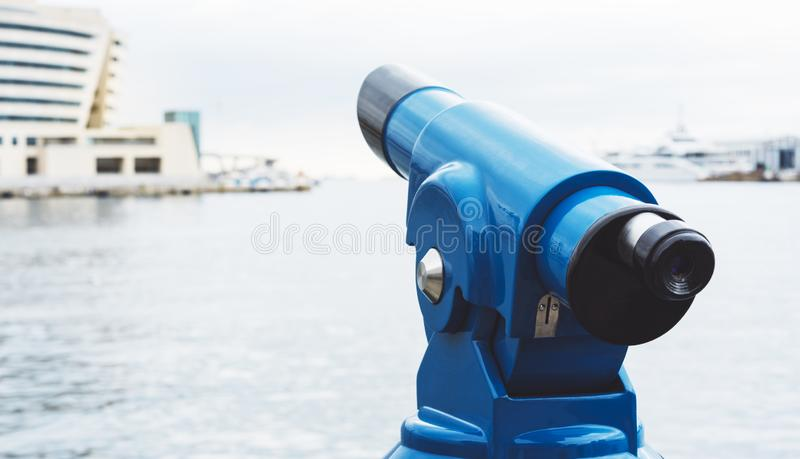 Touristic telescope look at city and sea with sunset view of Barcelona Spain, close up old blue binoculars on background viewpoint. The pier port yacht, coin royalty free stock image