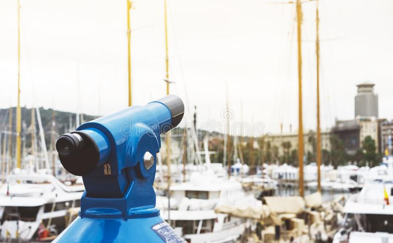 Touristic telescope look at the city with view of Barcelona Spain, close up old blue binoculars on background viewpoint. The pier port yacht, coin operated in royalty free stock photography