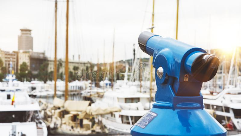 Touristic telescope look at the city with view of Barcelona Spain, close up old blue binoculars on background viewpoint the pier. Port yacht, coin operated in stock photos