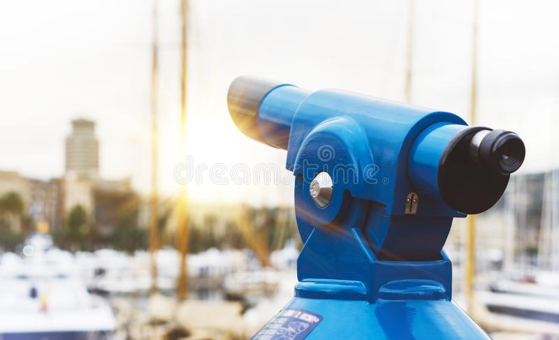 Touristic telescope look at the city with view of Barcelona Spain, close up old blue binoculars on background viewpoint the pier. Port yacht, coin operated in royalty free stock image