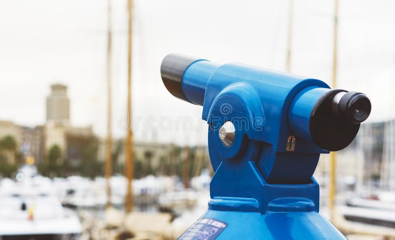 Touristic telescope look at the city with view of Barcelona Spain, close up old blue binoculars on background viewpoint the pier. Port yacht, coin operated in stock photography