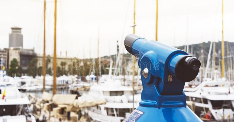 Touristic telescope look at the city with view of Barcelona Spain, close up old blue binoculars on background viewpoint the pier. Port yacht, coin operated in stock photo