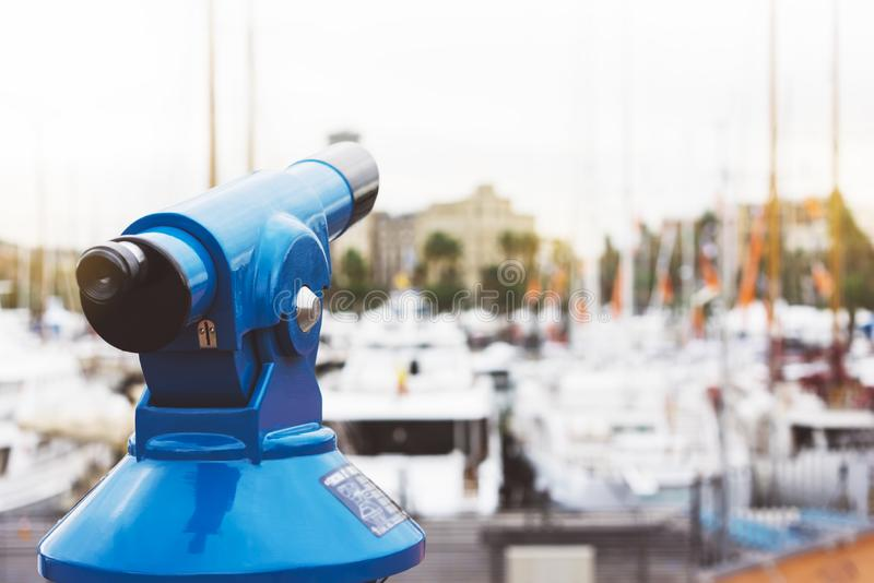 Touristic telescope look at the city with view of Barcelona Spain, close up old blue binoculars on background viewpoint the pier. Port yacht, coin operated in royalty free stock photos