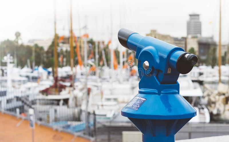 Touristic telescope look at the city with view of Barcelona Spain, close up old blue binoculars on background viewpoint the pier. Port yacht, coin operated in stock images