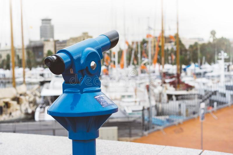 Touristic telescope look at the city with view of Barcelona Spain, close up old blue binoculars on background viewpoint the pier. Port yacht, coin operated in royalty free stock photography
