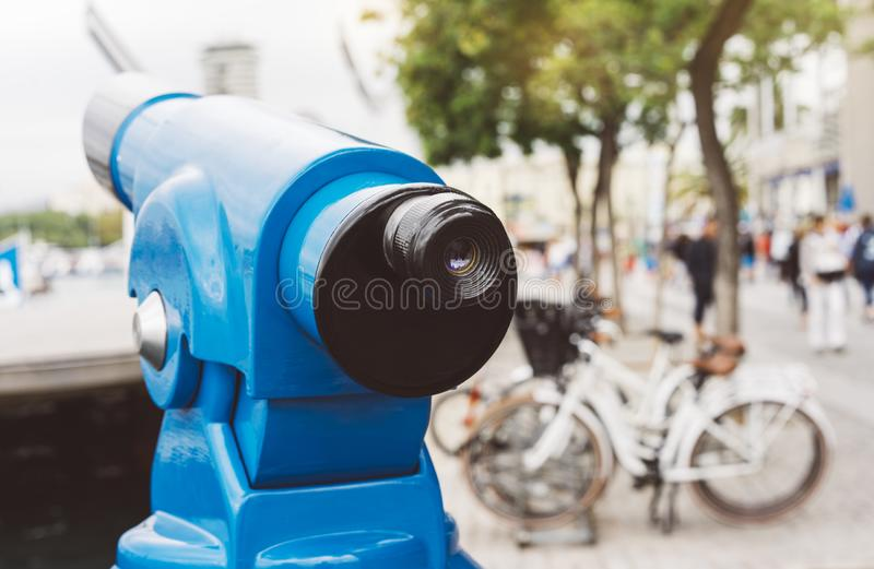 Touristic telescope look at the city with view of Barcelona Spain, close up old blue binoculars on background viewpoint the port. Yacht and cycle bike, coin stock image