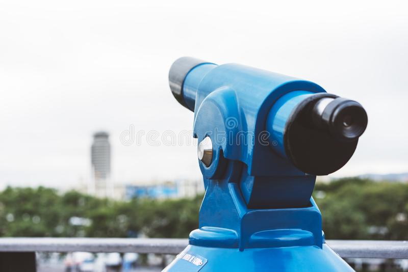 Touristic telescope look at the city with view of Barcelona Spain, close up old blue binoculars on green nature background view. Point, coin operated in panorama royalty free stock image